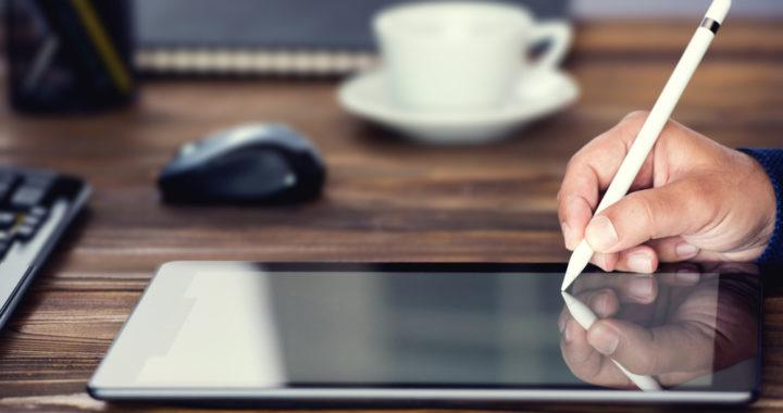 Mão portando uma caneta sobre tablet, fazendo uma assinatura eletrônica