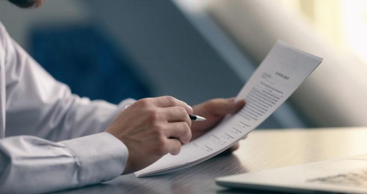 Homem analisando termos, procurando possível multa contratual