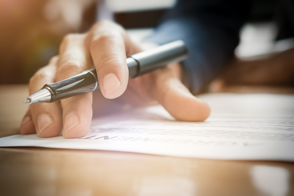 Mão com caneta sobre contrato de prestação de serviços educacionais